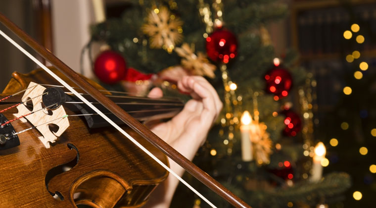 violinist playing holiday songs in front of christmas decorations