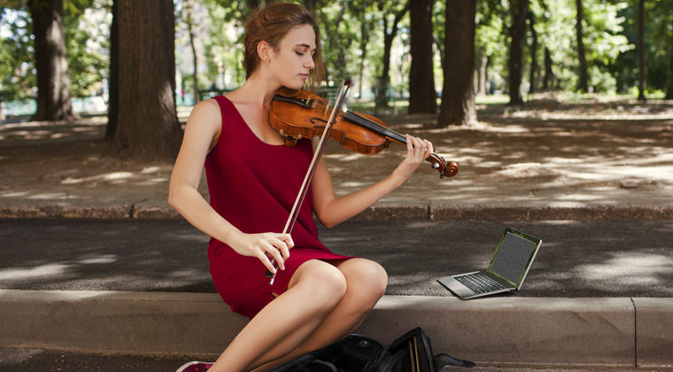 A lady practicing her instrument using the latest apps for violinists
