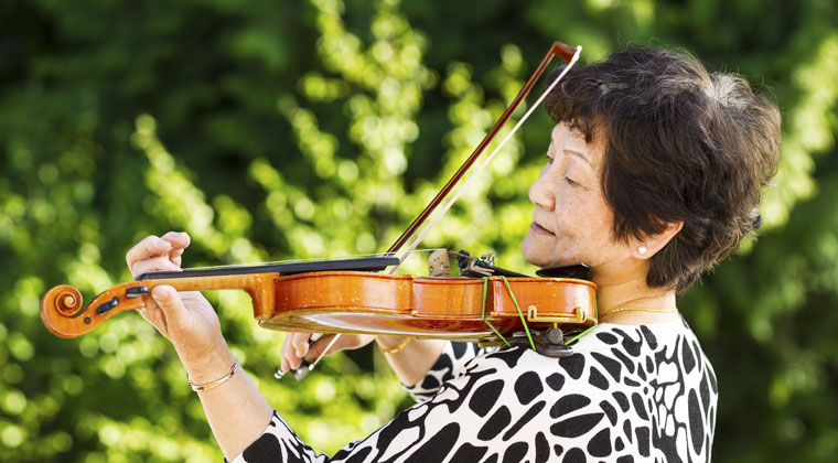 adult practicing the violin