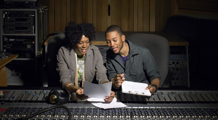 2 young people learning how to become sound engineers in the sound room