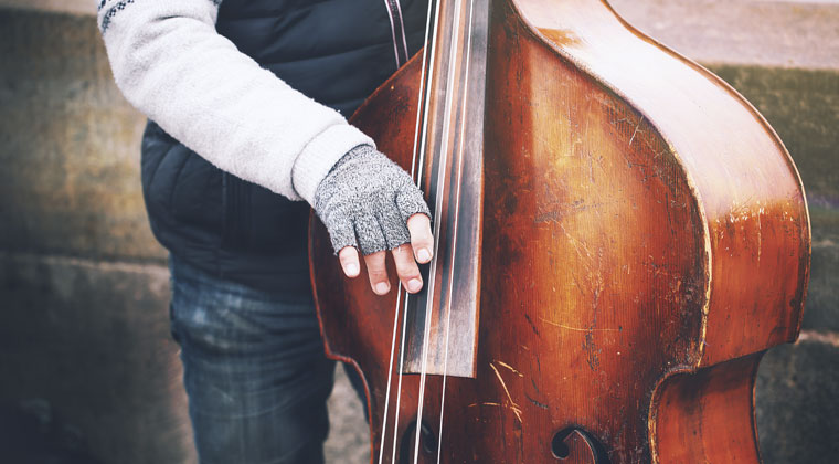 a musician wearing winter clothes while playing double bass outdoor