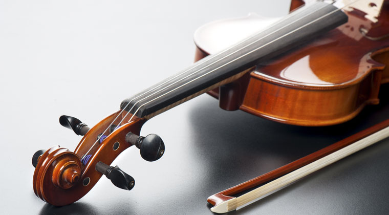 brand new violin with bow laying on table