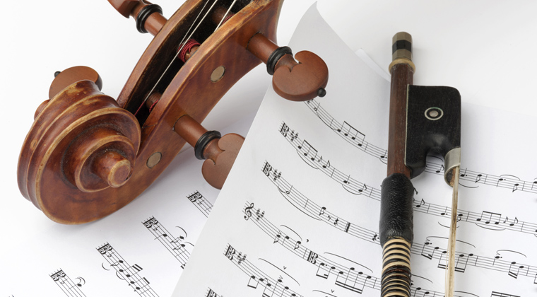 violin and bow on top of sheet music