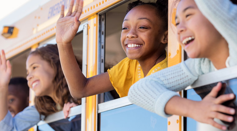 children waving out windows of school bus as they leave on a field trip